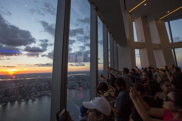 People photograph the sunset from One World Observatory, the observation deck at One World Trade Center, in Lower Manhattan, New York, September 11, 2015. (Photo by Andrew Kelly/Reuters)