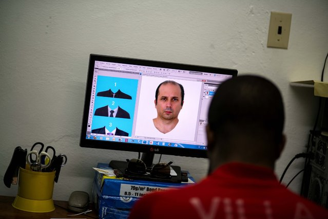 Lian Marrero edits a photo of Miami-based Cuban Javier Fontanella, with digital suit options at left, as he prepares his client's ID photo which he'll use for a Cuban citizenship application in Havana, Cuba, Thursday, May 26, 2016. Across Cuba and the world, tens of thousands of Cubans stare out of ID photos in elegant suits and dressy blouses they have never actually worn. (Photo by Ramon Espinosa/AP Photo)
