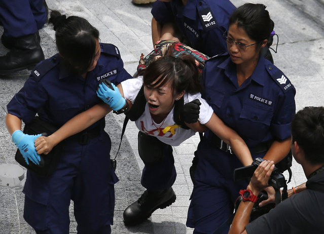 A protester reacts as she is dragged away by police after storming in government headquarters in Hong Kong September 27, 2014. (Photo by Bobby Yip/Reuters)