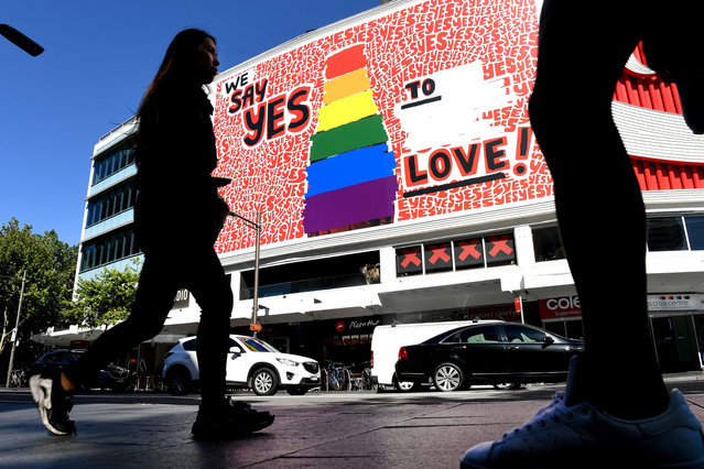 "People walk past a giant billboard in Sydney's Kings Cross district promoting the ""yes"" vote for same-s*x marriage on November 14, 2017. (Photo by William West/AFP Photo)"
