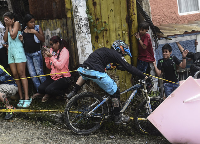 Residents look at a downhill rider crashing during the Urban Bike Inder Medellin race final at the Comuna 1 shantytown in Medellin, Antioquia department, Colombia on November 19, 2017. (Photo by Joaquin Sarmiento/AFP Photo)