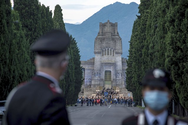 "Carabinieri officers patrol the road leading to the Bergamo cemetery, Italy, Sunday, June 28, 2020. Italy bid farewell to its coronavirus dead on Sunday with a haunting Requiem concert performed at the entrance to the cemetery of Bergamo, the hardest-hit province in the onetime epicenter of the outbreak in Europe. President Sergio Mattarella was the guest of honor, and said his presence made clear that all of Italy was bowing down to honor Bergamo's dead, ""the thousands of men and women killed by a sickness that is still greatly unknown and continues to threaten the world"". (Photo by Claudio Furlan/LaPresse via AP Photo)"