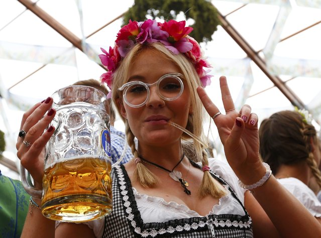 A visitor drinks beer on the first day of the 182nd Oktoberfest in Munich, Germany, September 19, 2015. (Photo by Michaela Rehle/Reuters)