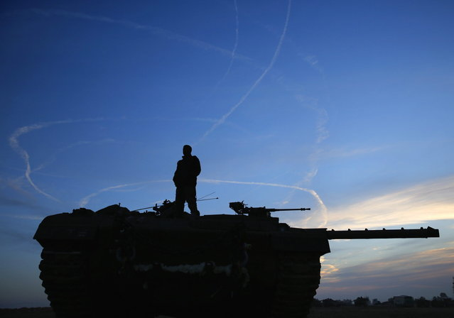 An Israeli soldier atop a tank looks at air force fighter jets circling overhead an Israeli Defence Forces (IDF) staging area in the northern Gaza border November 21, 2012. Israeli air strikes shook the Gaza Strip and Palestinian rockets struck across the border as U.S. Secretary of State Hillary Clinton held talks in Jerusalem in the early hours of Wednesday, seeking a truce that can hold back Israel's ground troops. (Photo by Yannis Behrakis/Reuters)