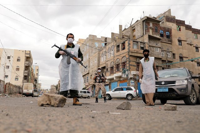 Security men wearing protective masks stand on a street during a 24-hour curfew amid concerns about the spread of the coronavirus disease (COVID-19), in Sanaa, Yemen on May 6, 2020. (Photo by Khaled Abdullah/Reuters)