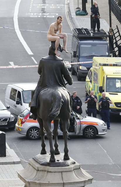 An unidentified man sits naked on top of the statue of Prince George, Duke of Cambridge outside the Ministry of Defence building in Whitehall in central London on November 23, 2012.  The man, who brought Whitehall to a standstill for almost two hours, stood naked on the statue and struck various poses before being eventually talked down. (Photo by Justin Tallis/AFP Photo)