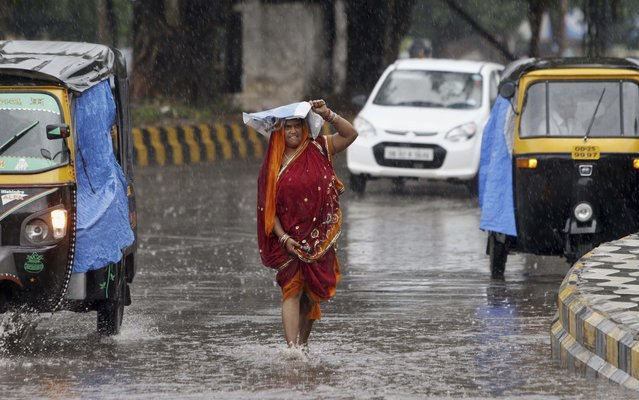 "An Indian woman shields herself with a plastic bag as she walks on a road in the rain, in Bhubaneswar, India, Friday, October 10, 2014. According to Indian Meteorological Department reports, severe cyclonic storm ""Hudhud"" is likely to hit Andhra Pradesh and Orissa coasts Sunday. (Photo by Biswaranjan Rout/AP Photo)"