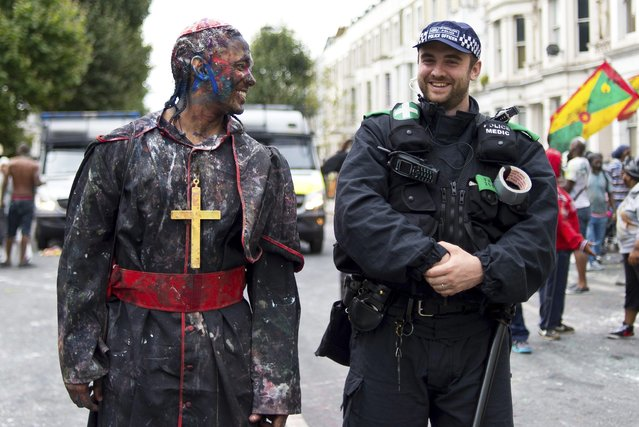 A reveller shares a joke with a police officer as Notting Hill Carnival begins on August 28, 2016 in London, England. (Photo by Ben A. Pruchnie/Getty Images)