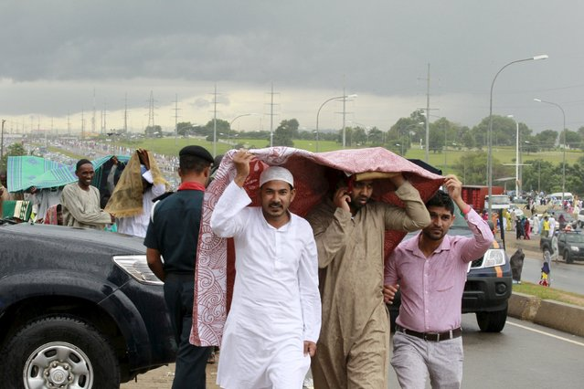 Men shelter themselves from the rain, after performing prayers during the Muslim festival of Eid-al-Adha in Abuja, Nigeria September 24, 2015. (Photo by Afolabi Sotunde/Reuters)