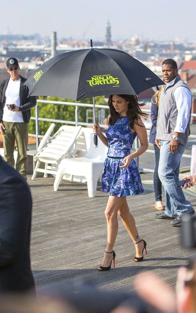 "Cast member Megan Fox arrives on a roof garden with an umbrella to avoid the sunlight for a photo call for the movie ""Teenage Mutant Ninja Turtles"" in Berlin October 5, 2014. (Photo by Hannibal Hanschke/Reuters)"