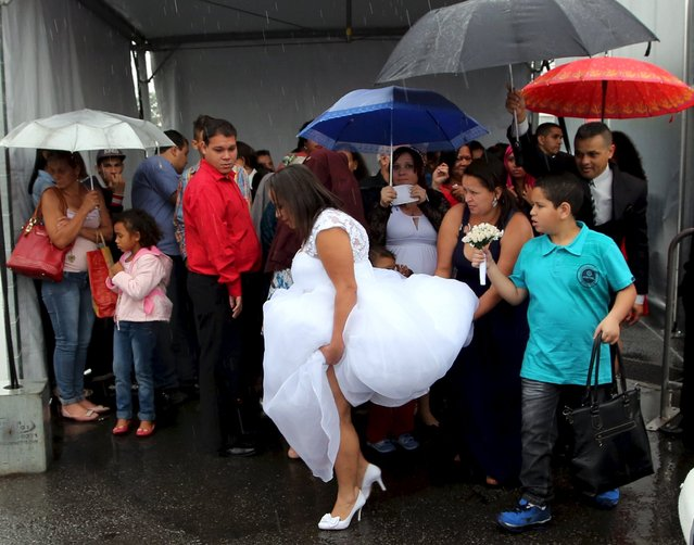 A bride is helped on her way to attend a mass wedding ceremony at Arena Corinthians soccer stadium in Sao Paulo, Brazil, September 26, 2015. According to the event's organizers, at least 400 couples tied the knot during a mass wedding which was organized by the Department of Justice and Citizenship of the state of Sao Paulo. (Photo by Paulo Whitaker/Reuters)