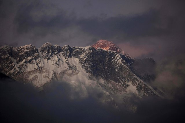 In this October 27, 2011 file photo, the last light of the day sets on Mount Everest as it rises behind Mount Nuptse as seen from Tengboche, in the Himalaya's Khumbu region, Nepal. Nepal is improving weather forecasting systems, stepping up security and promises swift rescues if needed during the upcoming climbing season on Everest in attempt to recover from the worst mountaineering disaster on the world's highest peak last year, officials said Monday. (Photo by Kevin Frayer/AP Photo)
