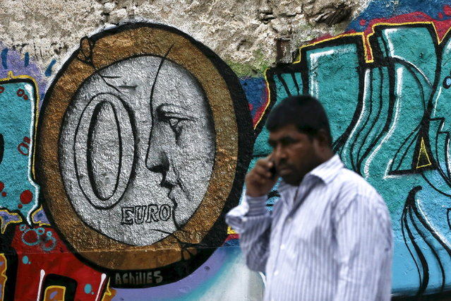 A man walks past a graffiti by Greek street artist Achilles, depicting a zero Euro coin in Athens, Greece, June 26, 2015. (Photo by Alkis Konstantinidis/Reuters)