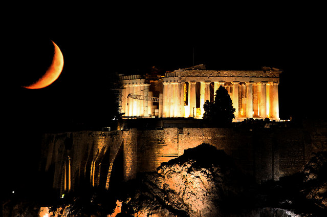 A crescent moon is seen behind the lit Temple of Parthenon atop the ancient Acropolis hill in central Athens, Greece, July 27, 2017. (Photo by Yannis Behrakis/Reuters)