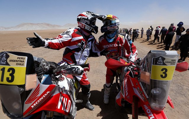 Honda riders Gerard Farres Guell of Spain, left, and Helder Rodrigues of Portugal talk at the end of  the special stage of the 2013 Dakar Rally's 5th stage from Arequipa, Peru, to Arica, Chile on Wednesday, January 9, 2013. (Photo by Victor R. Caivano/Associated Press)