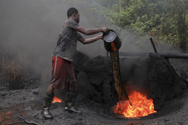 """A man working at an illegal oil refinery site pours oil under a locally made burner to keep the fire going, near river Nun in Nigeria's oil state of Bayelsa November 27, 2012. Thousands of people in Nigeria engage in a practice known locally as """"oil bunkering"""" – hacking into pipelines to steal crude then refining it or selling it abroad. The practice, which leaves oil spewing from pipelines for miles around, managed to lift around a fifth of Nigeria's two million barrel a day production last year according to the finance ministry. (Photo by Akintunde Akinleye/Reuters)"""
