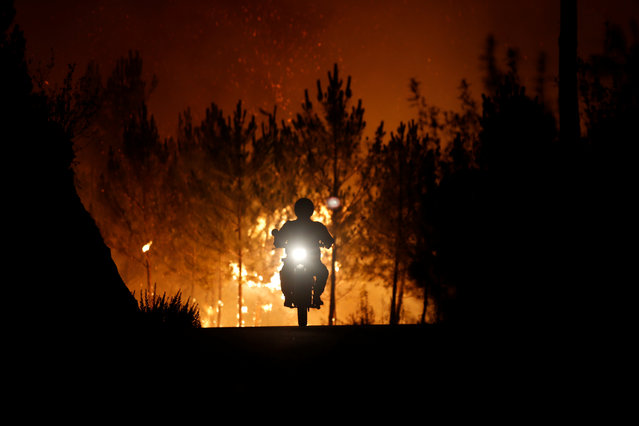 A firefighter rides a motorbike away from a forest fire next to the village of Macao, near Castelo Branco, Portugal, July 26, 2017. (Photo by Rafael Marchante/Reuters)