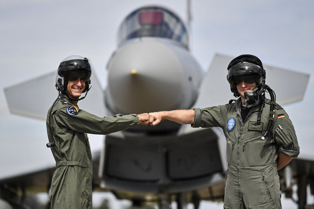 A pilot from Israel, left, and a pilot from Germany, right, pose in front of an Eurofighter at the airbase in Noervenich, Germany, Thursday, August 20, 2020. Pilots from Israel and Germany will fly together the next two weeks during the first joint military Air Force exercises between the two nations in Germany. (Photo by Martin Meissner/AP Photo)