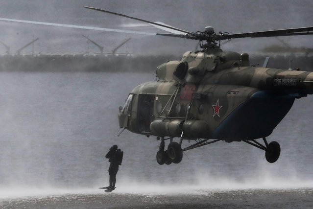 "A Russian serviceman jumps in the water from a Mi-8 MTV military helicopter during a demonstration show at the International military-technical forum ""Army-2020"" at Alabino range in Moscow Region, Russia, August 24, 2020. (Photo by Evgenia Novozhenina/Reuters)"