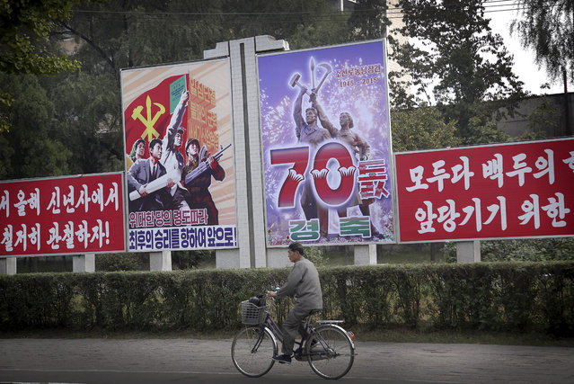 A man cycles past a signboard marking the upcoming 70th anniversary of the founding of North Korea's Workers' Party, Thursday, October 8, 2015, in Pyongyang, North Korea. (Photo by Wong Maye-E/AP Photo)