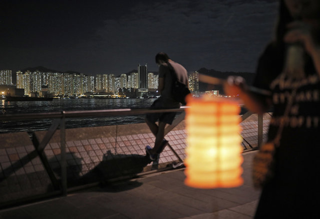 Residents hold up lanterns during the Chinese Mid-Autumn Festival at a park in Hong Kong, Friday, September 16, 2016. Like ancient Chinese poets, Hong Kong people appreciate the beauty of the full moon in the Mid-Autumn Festival. (Photo by Vincent Yu/AP Photo)
