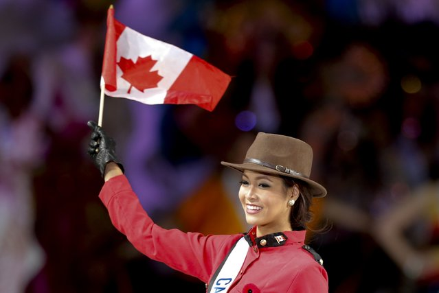 Kesiah Papasin of Canada waves a Canadian national flag as she poses in a costume similar to those used by the Royal Canadian Mounted Police during the 54th Miss International Beauty Pageant in Tokyo November 11, 2014. (Photo by Thomas Peter/Reuters)