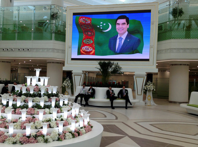 People sit inside the terminal of the newly built airport with a screen showing a portrait of Turkmen President Kurbanguly Berdymukhamedov during its official opening in  Ashgabat, Turkmenistan, September 17, 2016. (Photo by Marat Gurt/Reuters)