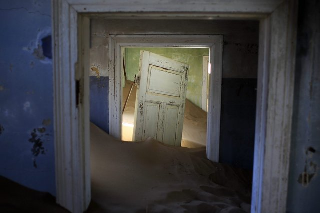 In this July 23, 2013 photo, sand fills an abandoned house in Kolmanskop, Namibia. Kolmanskop, was a diamond mining town south of Namibia, build in 1908 and deserted in 1956. SInce then, the desert slowly reclaims its territory, with sand invading the buildings where 350 German colonists and more than 800 local workers lived during its hay-days of the 1920s. (Photo by Jerome Delay/AP Photo)