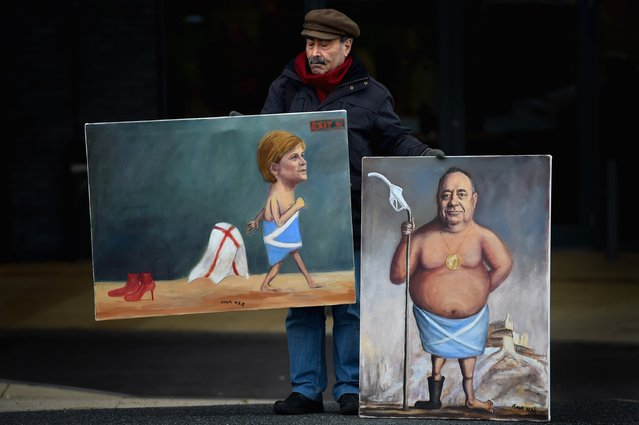 Artist Kaya Mar holds his paintings of First Minister Nicola Sturgeon and Alex Salmond MP outside the 81st SNP conference at the Aberdeen Exhibition and Conference centre on October 15, 2015 in Aberdeen, Scotland. Nicola Sturgeon will use her opening speech at the SNP conference to call on people who rejected independence in the referendum to vote for her party in next year's Holyrood election. (Photo by Jeff J. Mitchell/Getty Images)