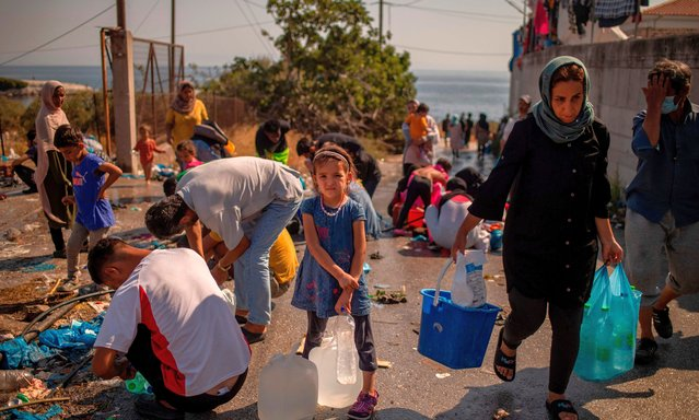 A girl waits to fill bottles with water near a temporary migrant camp on the Greek Aegean island of Lesbos on September 16, 2020, after the Moria camp was destroyed by a fire on the night of September 8. Six young Afghan men including two minors will face a prosecutor on Greece's Lesbos island on September 16 on suspicion of setting fires that destroyed Europe's largest migrant camp, leaving over 12,000 people homeless. (Photo by Angelos Tzortzinis/AFP Photo)