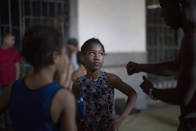 A wrestling teacher gives instructions to a child during a lesson in downtown Havana, November 11, 2014. (Photo by Alexandre Meneghini/Reuters)