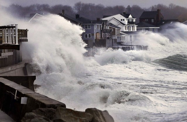 Ocean waves crash over a seawall and into houses along the coast in Scituate, Massachusetts, March 7, 2013. A nor'easter is bringing wind-whipped, wet snow to the state, and coastal flooding is expected in communities still recovering from February's blizzard. (Photo by Steven Senne/Associated Press)