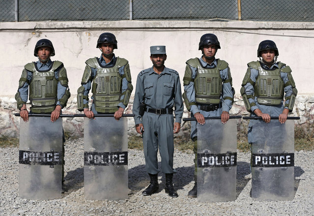 "Afghan anti-riot policemen (R-L)  Habib, 21, Sayed Rahman, 22, Mohammad Nabi, 22, Momin Khan, 22, and Abdul Ali, 25, pose for photo at their base in Kabul October 12, 2014. In Afghanistan, ""the police can use weapons or explosives against a group of people only if they it has ... disturbed security by means of arms, and if the use of other means of force ... has proved ineffective"". Afghan police are required to give no fewer than six warnings – three verbal and three warning shots - before using force in this situation. (Photo by Omar Sobhani/Reuters)"