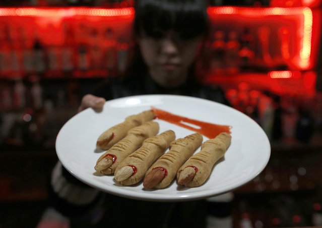 A waitress shows cookies in the shape of chopped fingers which is served at the V bar during a photo opportunity in Beijing November 28, 2014. The Vampire-themed bar serves unique foods such as a chocolate in the shape of an eyeball and cocktails in syringes and blood bags, in a place decorated like a vampire base of the Middle Ages. (Photo by Kim Kyung-Hoon/Reuters)