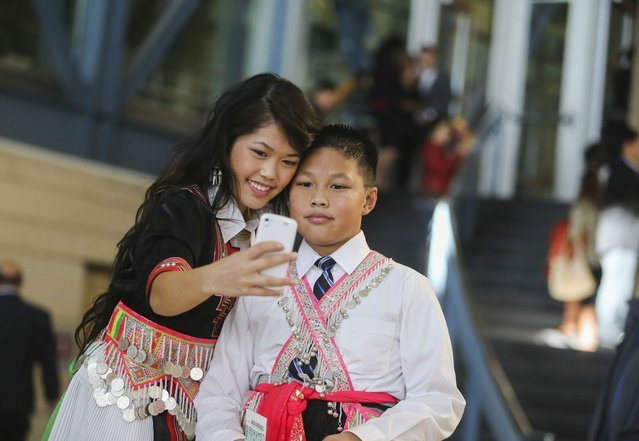 Pashoua Herr, 19, of Minneapolis, takes a selfie with her brother Jonathan Herr, 11, at the Minnesota Hmong New Year celebration Saturday, November 29, 2014, at the Saint Paul RiverCentre in St. Paul, MN. (Photo by David Joles/Star Tribune)