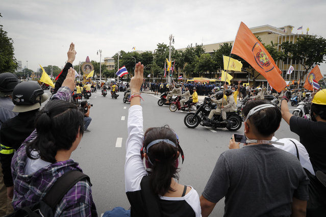 Anti-government protesters raise three-finger salutes, a symbol of resistance, during a protest near the Democracy Monument in Bangkok, Thailand, Wednesday, October 14, 2020. (Photo by Gemunu Amarasinghe/AP Photo)