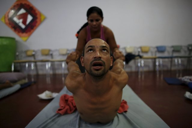 An occupational therapist (back) conducts an Ayurvedic massage on prisoner Anderson Miranda, 33, as part of the ACUDA programme, at a complex of ten prisons in Porto Velho, Rondonia State, Brazil, August 27, 2015. (Photo by Nacho Doce/Reuters)