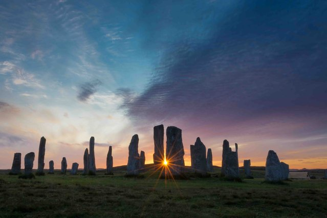 "Callanish Sunburst, Isle of Lewis. Classic View youth winner. ""We had just arrived on Lewis for a family holiday when we noticed the sky was looking interesting and there was potential for a good sunset. We jumped in the car and drove the very short distance to Callanish where I joined all the tourists, just as the sun slowly set behind the standing stones. It was just about to disappear over the horizon when I caught this little sunburst"". (Photo by Andrew Bulloch/UK Landscape Photographer of the Year 2020)"