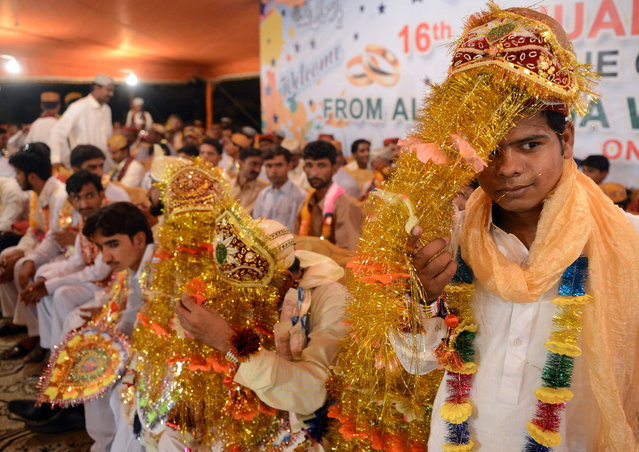 Pakistani grooms attend a mass marriage ceremony in Karachi late March 26, 2013.  Some 110 couples participated in the mass wedding ceremony organised by a local charity welfare trust Al Ghousia. (Photo by Asif Hassan/AFP Photo)