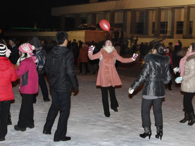 """North Koreans play with a balloon as they wait outside Pyongyang stadium for the countdown to the new year on Monday, December 31, 2012. North Koreans celebrated the arrival of the new year, marked as """"Juche 102"""" on North Korean calendars. """"Juche"""" means """"self reliance"""", the North Korean ideology of independence promoted by North Korean founder Kim Il Sung, and modern-day North Korean calendars start with the year of his birth in 1912. (Photo by Kim Kwang Hyon/AP Photo)"""