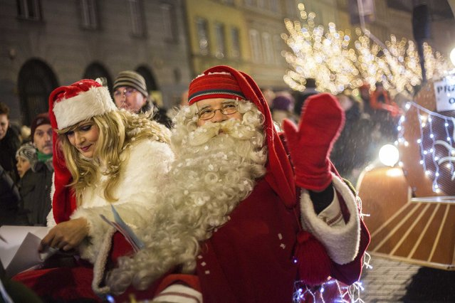 A man dressed like Santa Claus waves as he takes part in a parade during the annual illumination of Christmas lights in Warsaw December 6, 2014. (Photo by Bartosz Bobkowski/Reuters/Agencja Gazeta)