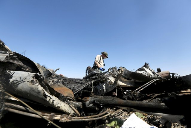 A military investigator from Russia stands near the debris of a Russian airliner at the site of its crash at the Hassana area in Arish city, north Egypt, November 1, 2015. (Photo by Mohamed Abd El Ghany/Reuters)
