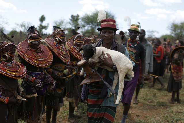 A Pokot man holds a lamb as he blesses over a hundred girls during an initiation ceremony marking the girls' passing over into womanhood, about 80 km (50 miles) from the town of Marigat in Baringo County December 6, 2014. (Photo by Siegfried Modola/Reuters)