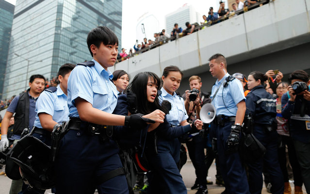 A demonstrator is taken away by policewomen from an area previously blocked by pro-democracy supporters, outside the government headquarters in Hong Kong, December 11, 2014. (Photo by Tyrone Siu/Reuters)