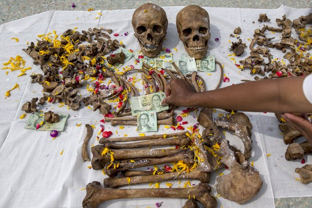 A volunteer puts a banknote on remains for luck during a mass exhumation at Poh Teck Tung Foundation Cemetery in Samut Sakhon province, Thailand November 3, 2015. (Photo by Athit Perawongmetha/Reuters)