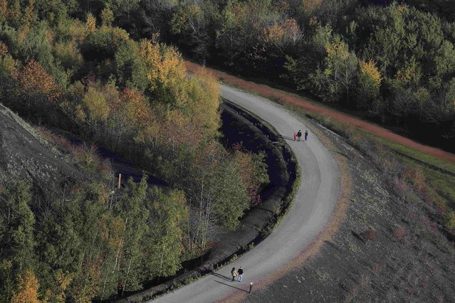 Hikers are seen on the path of the 11/19 pit and twin slag heaps at the former coal mine site in Loos-en-Gohelle, northern France, October 31, 2015. (Photo by Pascal Rossignol/Reuters)