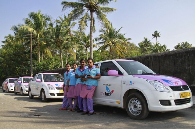 """Female drivers from the """"She Taxi"""" service pose next to a taxi on a road in the southern Indian city of Kochi, December 12, 2014. The alleged rape of a woman passenger by an Uber taxi driver once again spotlights the risks of India's transport system, which fails to keep women safe. (Photo by Sivaram V./Reuters)"""