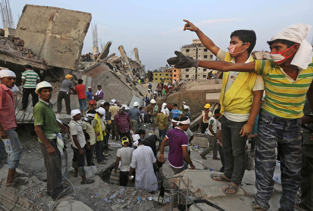 Bangladeshi rescuers from a youth group gesture for help at the site of a building that collapsed Wednesday in Savar, near Dhaka, Bangladesh, Thursday, April 25, 2013. By Thursday, the death toll reached at least 194 people as rescuers continued to search for injured and missing, after a huge section of an eight-story building that housed several garment factories splintered into a pile of concrete. (Photo by Kevin Frayer/AP Photo)