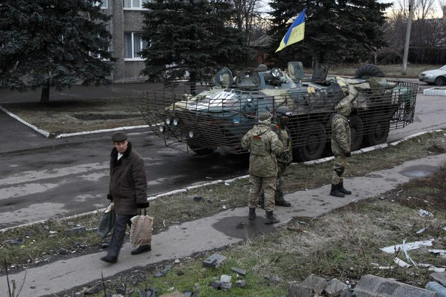 A man walks past Ukrainian servicemen in the eastern Ukrainian town of Debaltseve in Donetsk region, December 24, 2014. (Photo by Valentyn Ogirenko/Reuters)