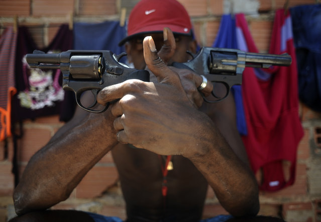 A Brazilian drug gang member nicknamed Pilintra, 26, poses with a gun atop a hill overlooking a slum in Salvador, Bahia State, April 11, 2013. One of Brazil's main tourist destinations and a 2014 World Cup host city, Salvador suffers from an unprecedented wave of violence with an increase of over 250% in the murder rate, according to the Brazilian Center for Latin American Studies (CEBELA). (Photo by Lunae Parracho/Reuters)